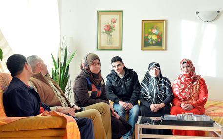 La famiglia Mounla all'interno dell'appartamento messo a disposizione dalla parrocchia Santi Pietro e Paolo, Torino, 1° marzo 2016.