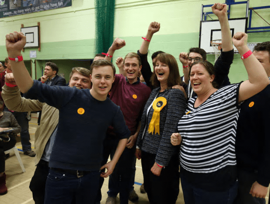 Lib Dem candidate Liz Leffman (with large rosette) and supporters at the Witney byelection count [Image: Chris Radburn/PA].