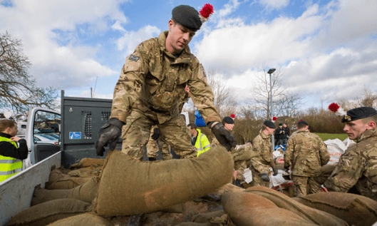 Soldiers unload sandbags after flooding in Wraybury in February 2014 [Image: Graeme Robertson for the Guardian].