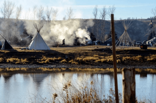 A person walks past smoke from a cooking fire at an encampment during a protest against the Dakota Access pipeline on the Standing Rock Indian Reservation near Cannon Ball, North Dakota, U.S. November 9, 2016 [Image: Reuters/Stephanie Keith].