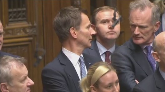 Jeremy Hunt shuffles uncomfortably under the gaze of his fellow MPs as Jeremy Corbyn asks why he is piloting a pointless scheme to harm NHS patients while claiming to be eliminating almost-non-existent 'health tourism'.