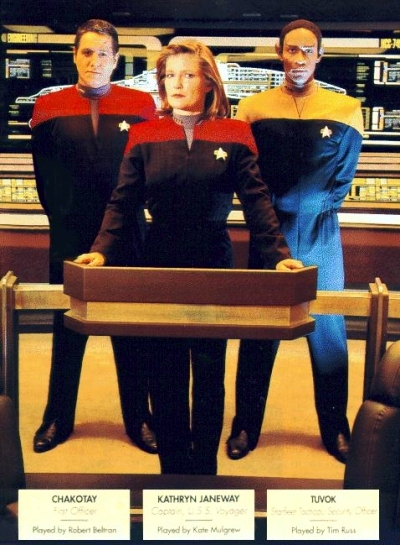 The command trio: Janeway in centre, Chakotay at her right, Tuvok at her left. It's a serious business publicity photo.