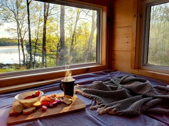 Café du matin et plateau de petit déjeuner disposés sur un lit douillet avec charmante vue sur un lac.
