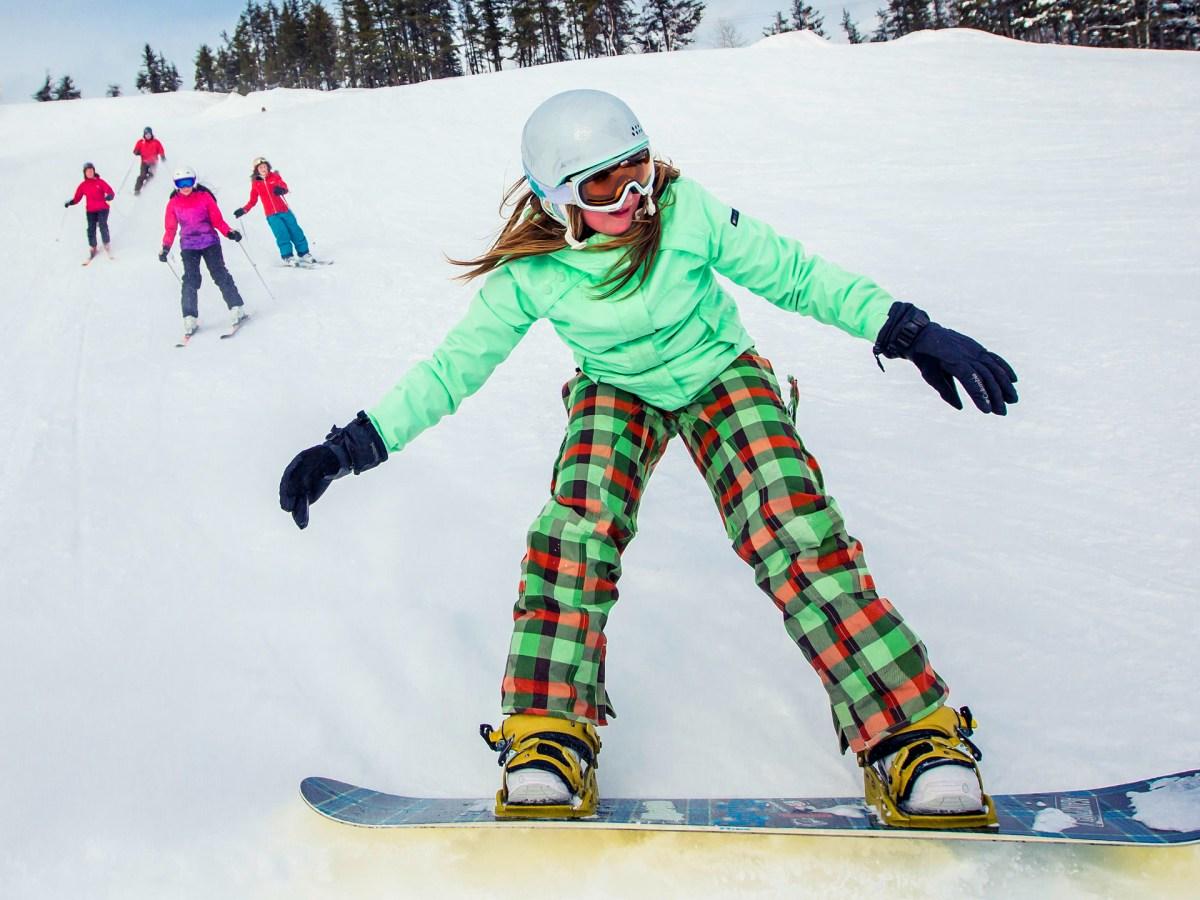 Jeune fille faisant de la planche à neige sur une pente avec une famille en ski derrière elle.