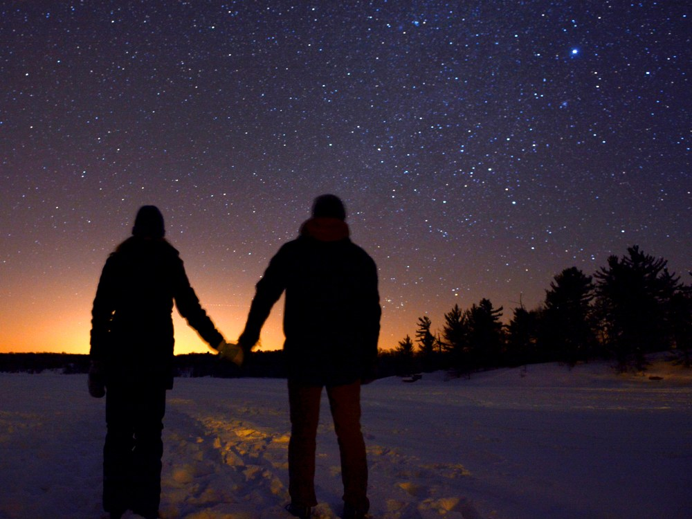 un couple se tenant la main tout en regardant le ciel étoilé à Muskoka.
