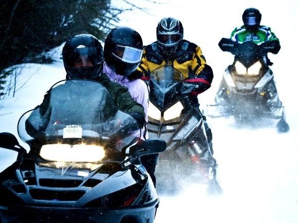 Quatre personnes l'une derrière l'autre en motoneige.