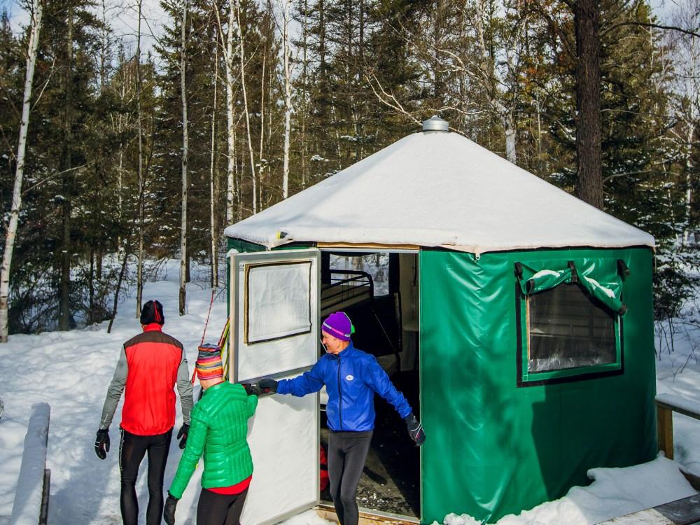 Trois personnes sortant d'une yourte dans le parc provincial Windy Lake