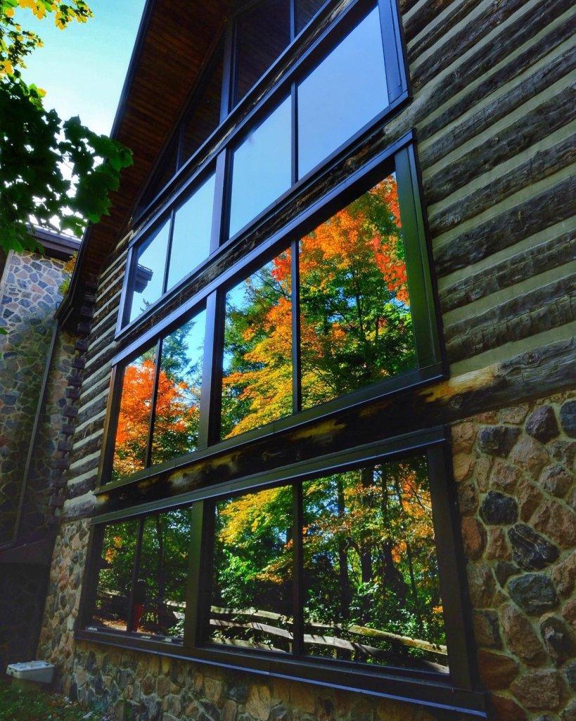 Les couleurs d'automne de la forêt se reflètent dans les vastes fenêtres du musée Collection McMichael d'art canadien