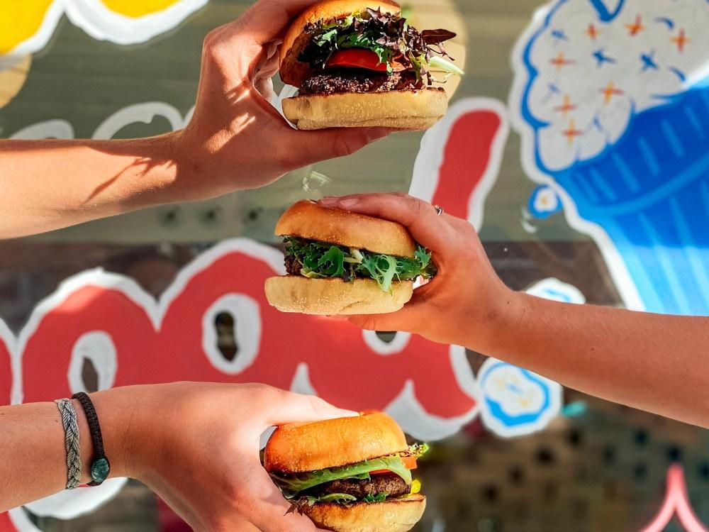 Trois personnes tenant des burgers qui semblent délicieux
