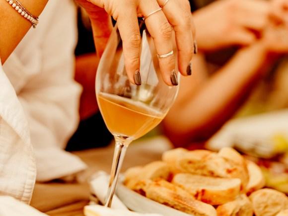 Femme tenant un verre de vin à table