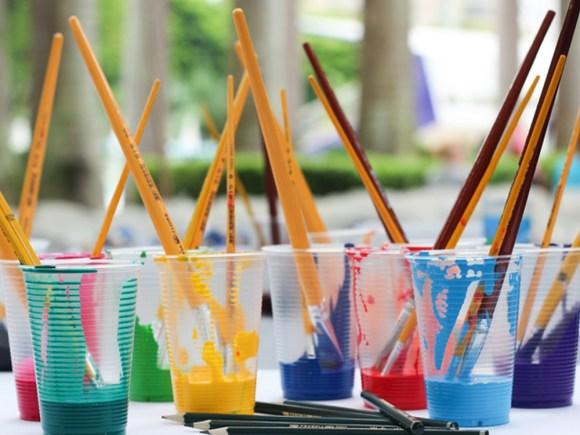Diverses tasses de peinture avec des pinceaux