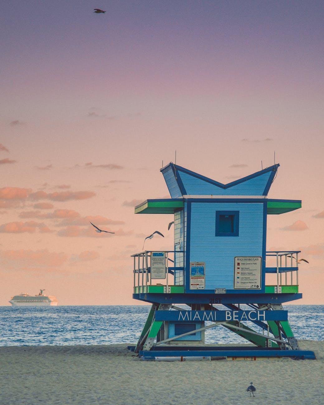 lifeguard building on seashore against sundown sky