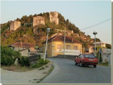 Route traversant Stolac : vue d'une maison et du château en ruines