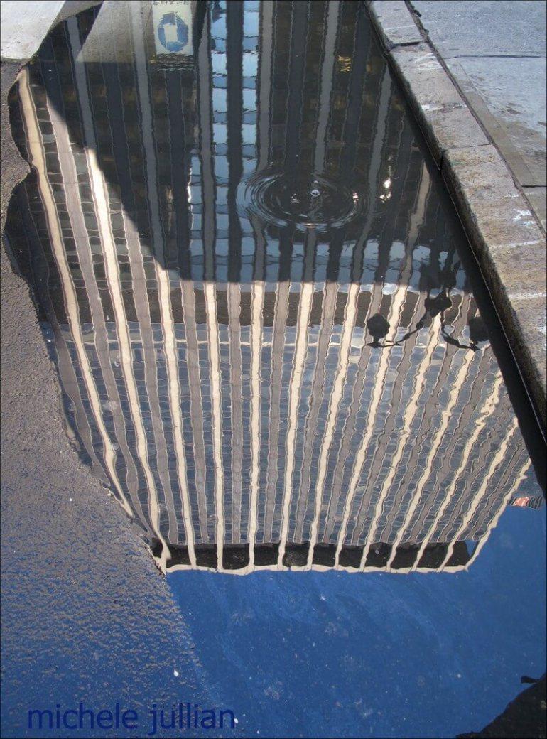 reflets du gratte ciel dans une flaque sur le trottoir à new york