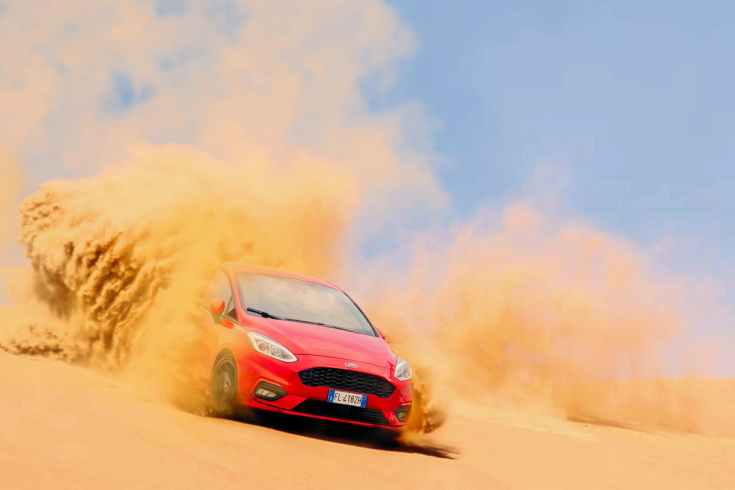 red ford focus vehicle driving on sand under blue daytime sky