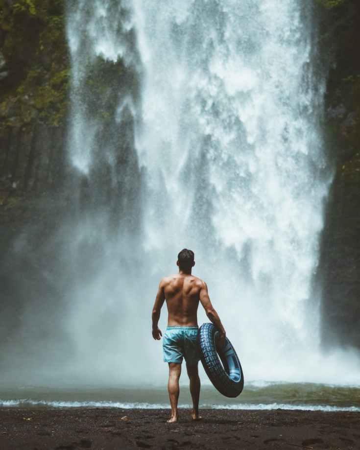 man wearing blue shorts holding vehicle tire facing waterfalls