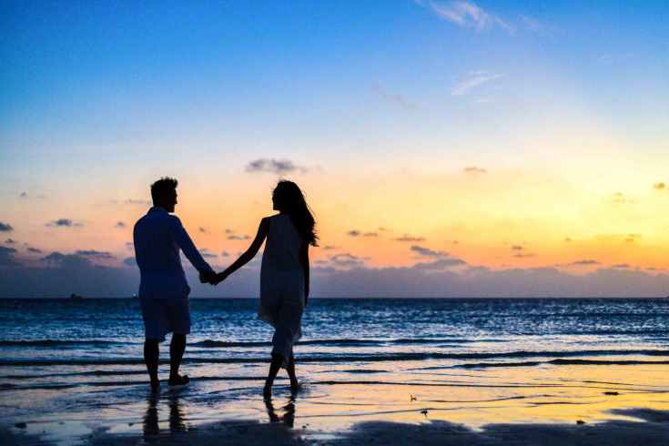 man and woman holding hands walking on seashore during sunrise