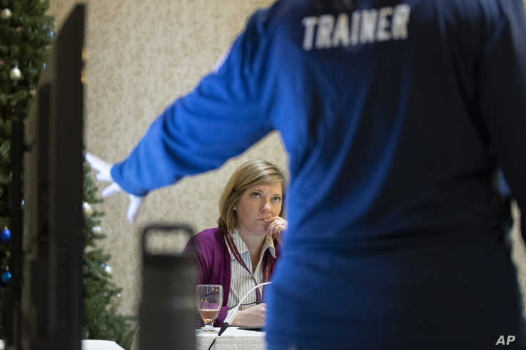 In this Monday, Dec. 16, 2019, photo, Karen Brenson Bell, from North Carolina, listens during an exercise run by military and…