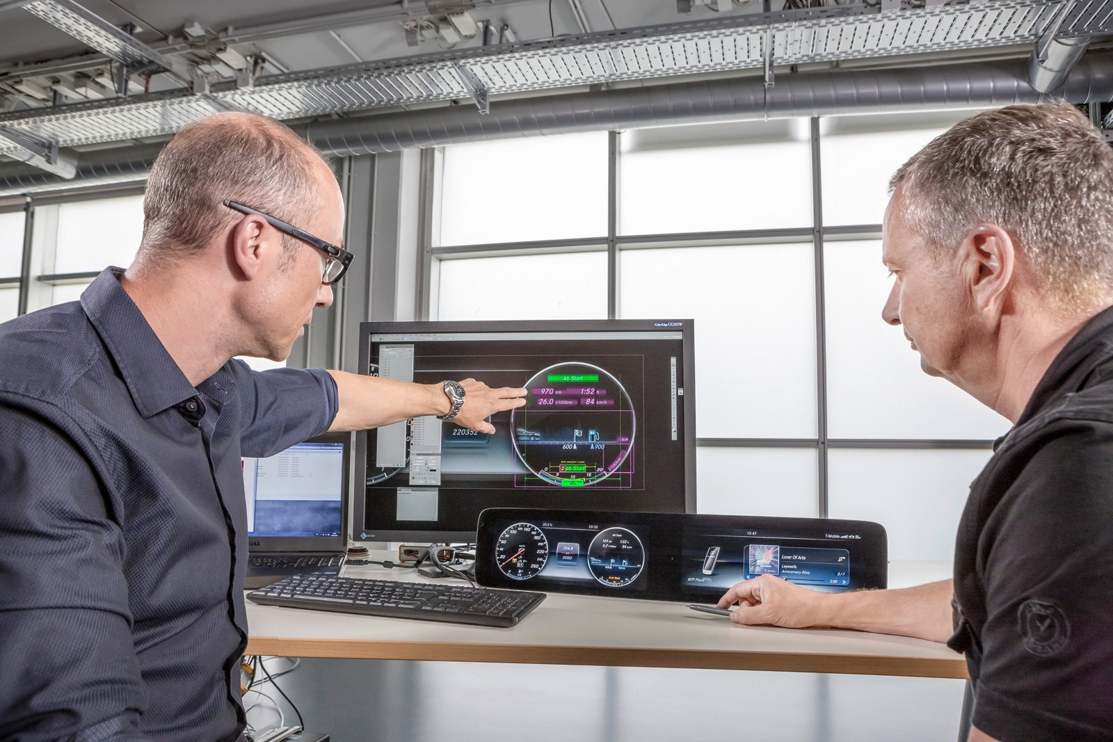Engineers from two new design-focused business units of Mercedes Benz are discussing how to implement new technology into the E-Class dual-display design.