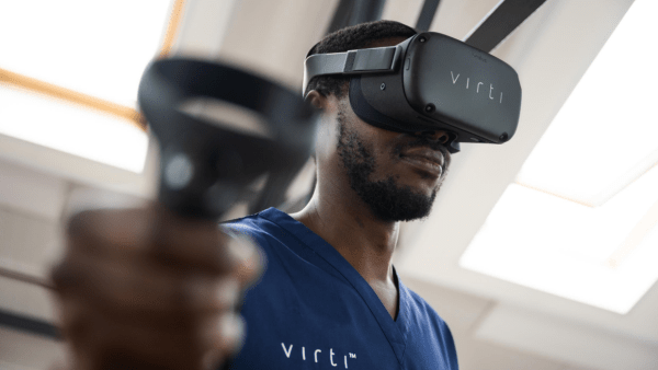 A nurse wearing a VR headset and training on the Virti platform