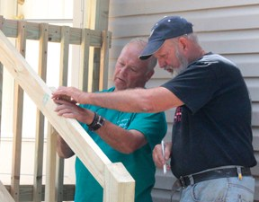 Bill Bechtoldt and Glenn Pike of Hazlet, New Jersey work to install a railing on a porch in the Weston Trailer Park. At home, Glenn is a full-time contractor. VTD Photo/Taylor Dobbs