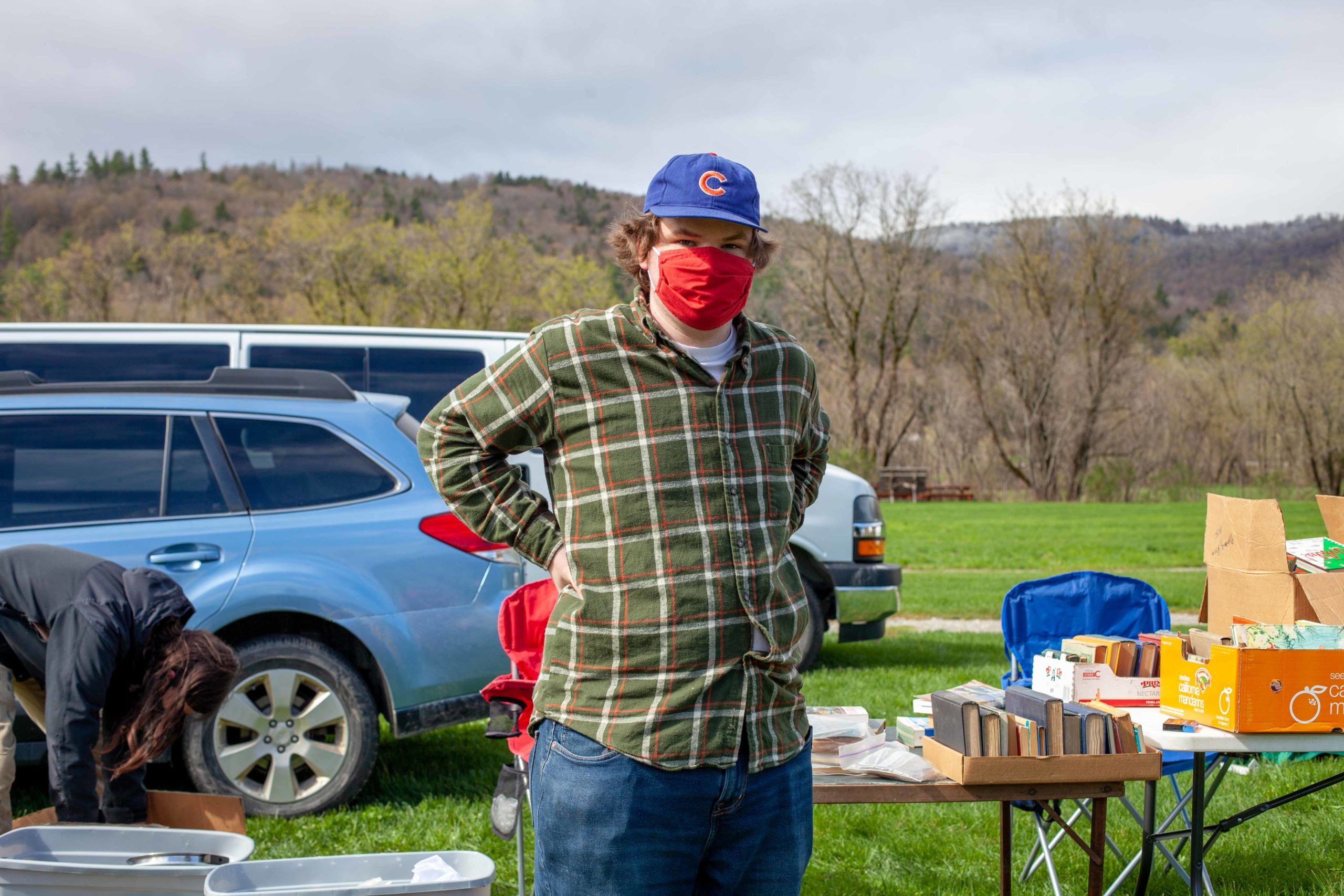 Man in Cubs baseball cap with hands on hips in front of tables of books