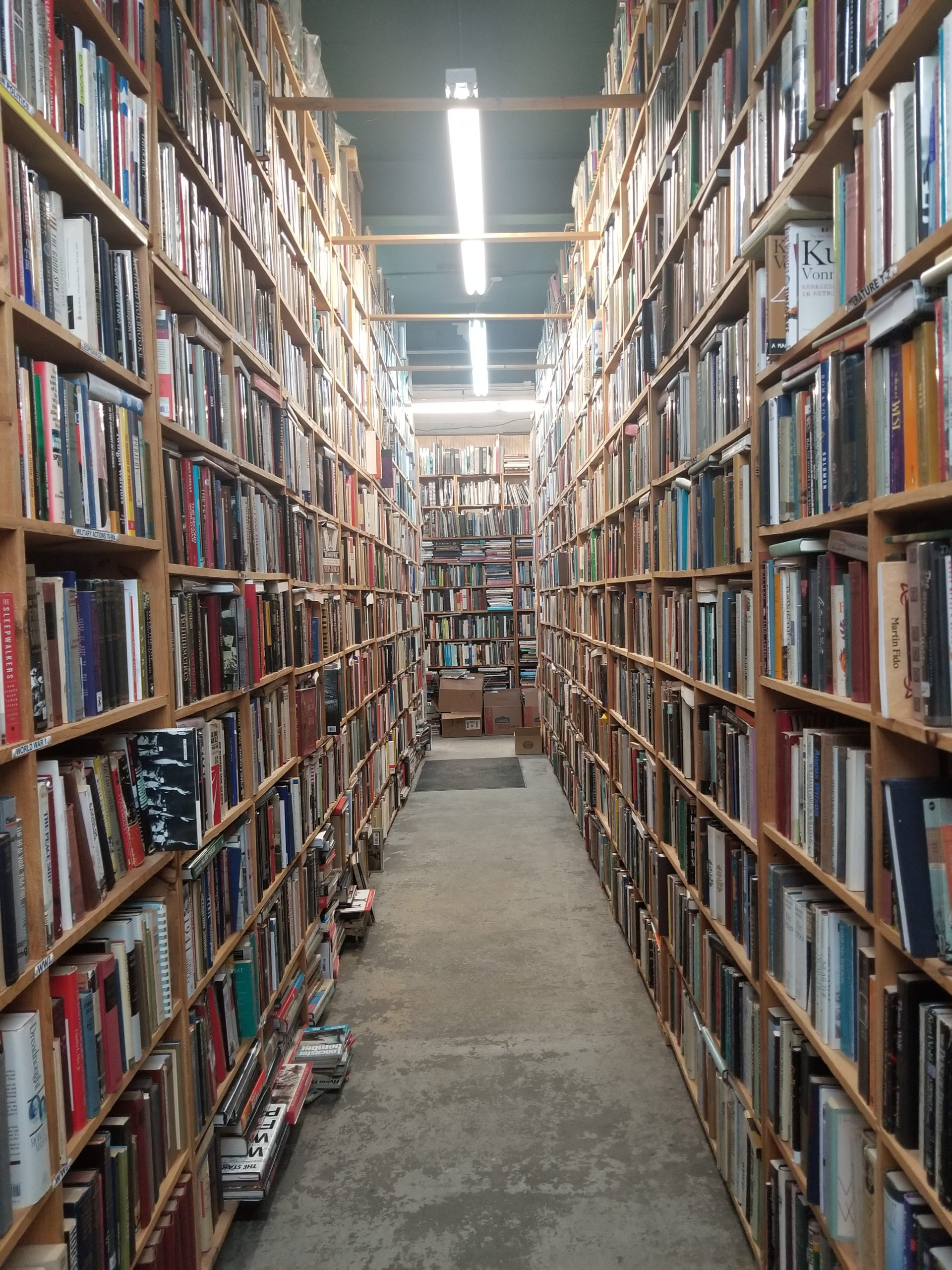 Aisle of used books on floor to ceiling shelves