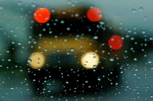 View of a school bus through a rainy window.