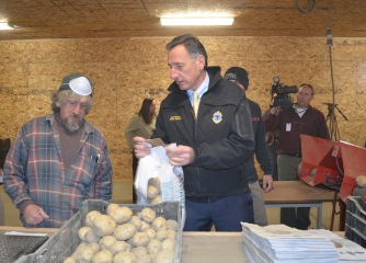 An inmate at Southeast State Correctional Facility shows Gov. Peter Shumlin how to properly weigh a bag of potatoes during processing in November 2012. Photo by Alicia Freese