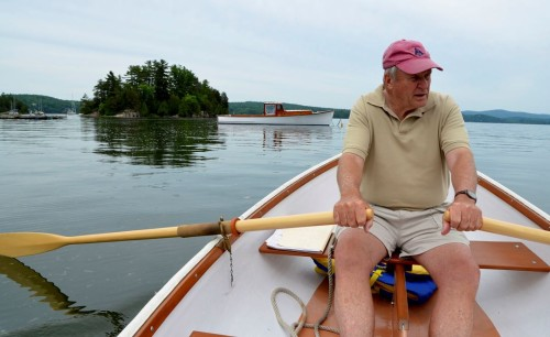 Jan Rozendaal rows out in a dory on Malletts Bay to his newest restored wooden craft, an iconic Maine lobster boat named the Maddy Sue. Photo by Andrew Nemethy