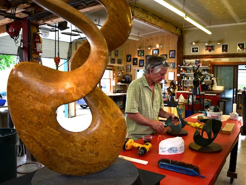 Sculptor Richard Erdman works in his studio, framed by one of his unusual twisting stone pieces. He has produced more than 1,000 sculptures and his works, from small to mammoth, have ended up in museums, galleries and corporate and private sites around the world. Photo by Andrew Nemethy/VTDigger