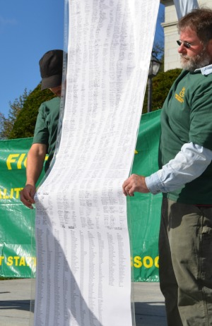 A petition with 1,200 signatures is held up at a rally organized by the Vermont State Employees Association, which represents some 250 Vermont State Colleges workers. Photo by Alicia Freese/VTDigger