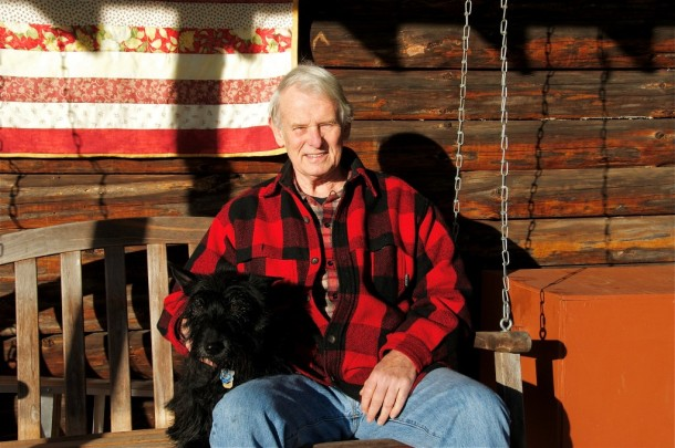 John McClaughry with his dog Lassie on the porch of his log home in Kirby. Photo by Dirk Van Susteren