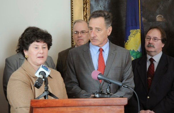 Department of Financial Regulation Commissioner Susan Donegan (left foreground) speaks with Gov. Peter Shumlin (right foreground) at the bill-signing ceremony for Vermont's Legacy Insurance Management Act. Reps. Warren Kitzmiller, D-Montpelier, and Mike Marcotte, R/D-Newport, also join. Photo by Hilary Niles/VTDigger.org