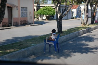 A little Dominican boy sits in a plastic chair, unattended, in the road on a side street in Nagua. He appears perfectly safe. Photo by Bob Stannard
