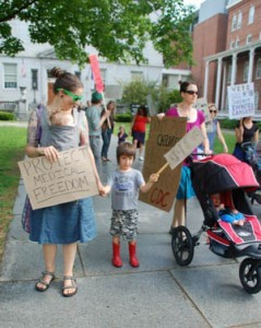 Morgan LaCroix of Bolton, with her son, James, 5, and her daughter, Hazel, six months, takes part in a protest of H.98, recently passed legislation that will take away the philosophical exemption to allow families to not vaccinate their children for school entry. Photo by Amy Ash Nixon/VTDigger