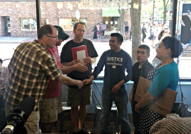Rob Michalak, Ben & Jerry's  global director of social mission, shakes hands with dairy farm worker Victor Diaz. Brendan O'Neill, director of Migrant Justice, is in center with red folder. Photo courtesy Keith Brunner