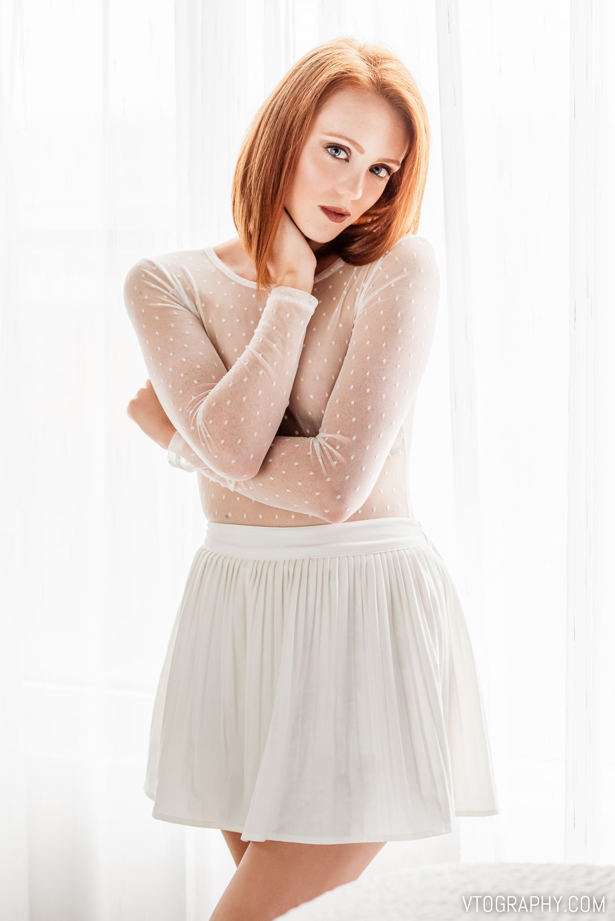 Redhead model Ashley in sheer top and white skirt