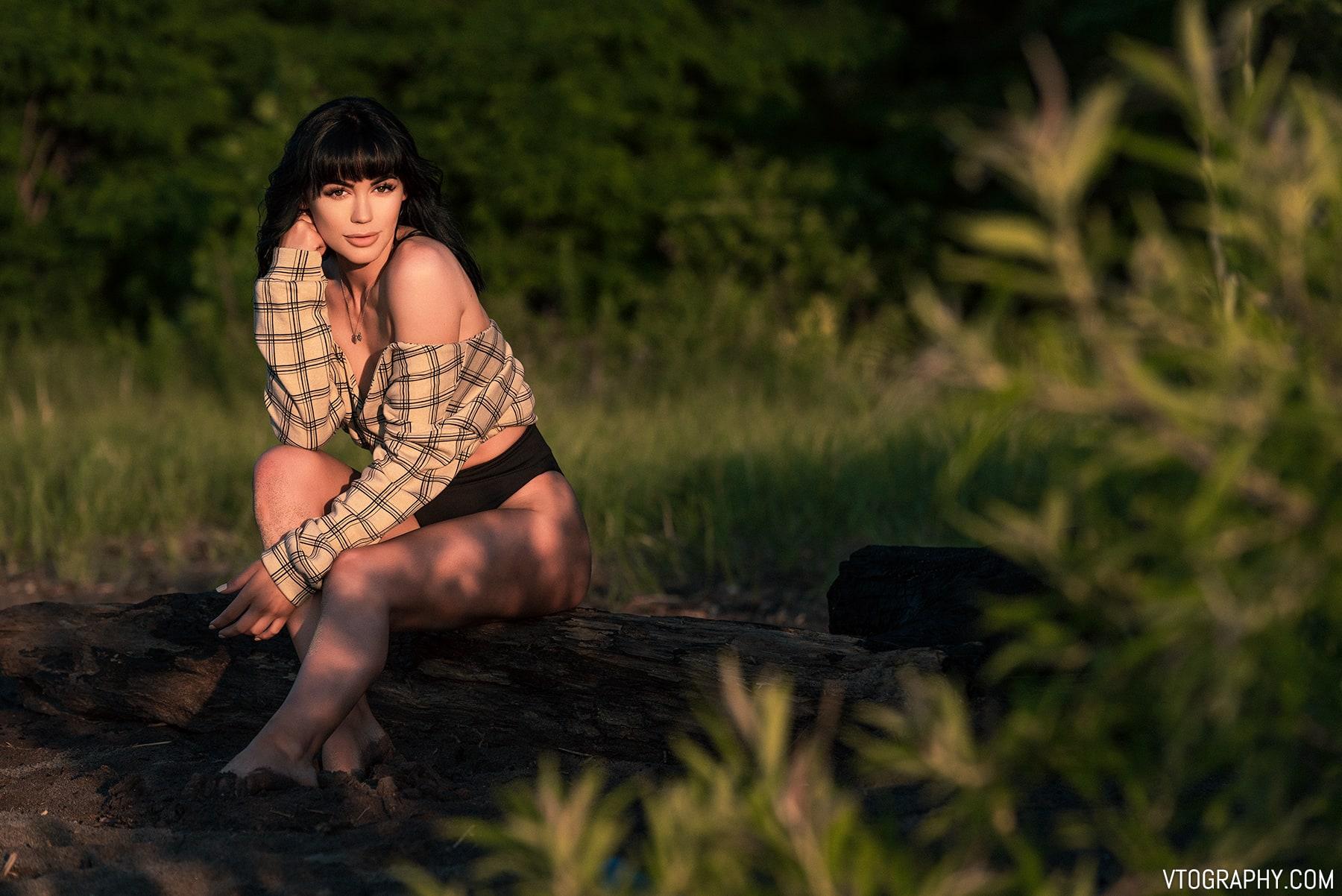 Model sitting on a log with a plaid shirt