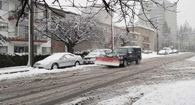 圖:大溫地區12 月5 日遭到三年來首場大型暴風雪,難得一見的大雪令路上交通大打結。圖為街道上的積雪和剷雪車。(攝影:王佳圓/看中國)