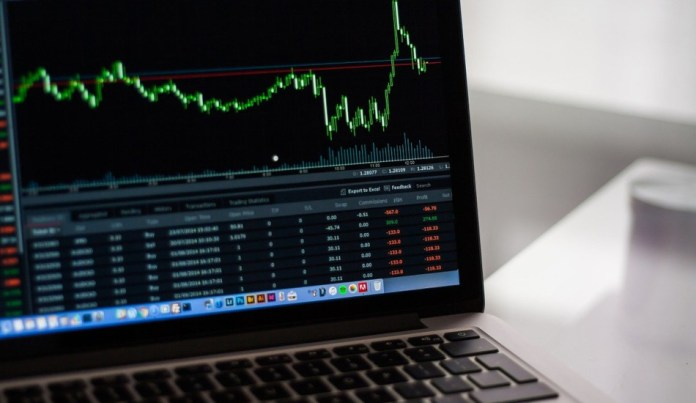 A laptop screen showing a candlestick chart.
