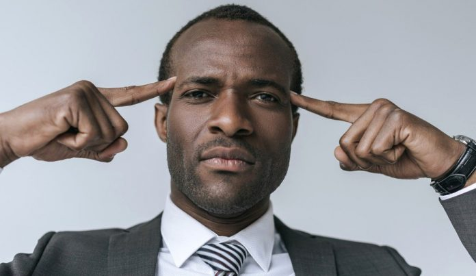 A man in a suit points his index fingers at his brain.