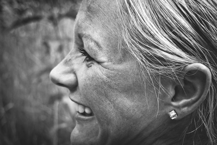 older womans face smiling this photo is black and white and shot from the side so we see her ears