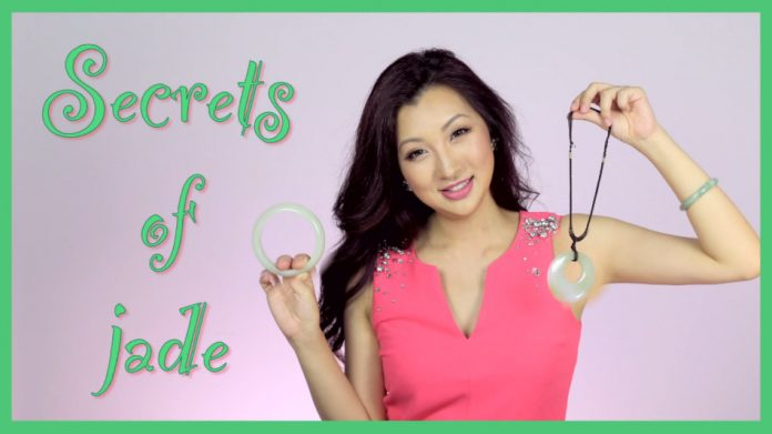 An Asian woman holding a jade bracelet and necklace.