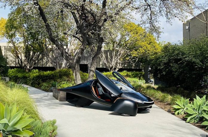 The three-wheeled Aptera Electric Vehicle in black, sitting on pavement in front of a tree.