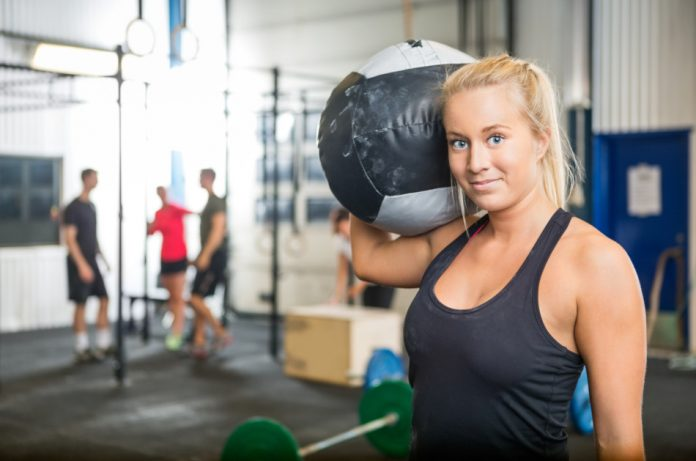 Fit woman carrying medicine ball at crossfit gym.