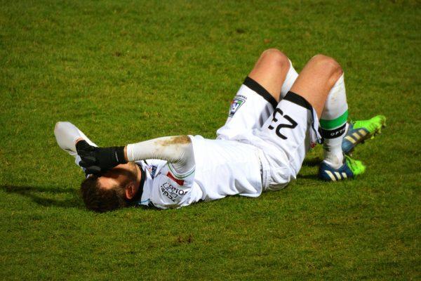 footballer lays on ground after injury