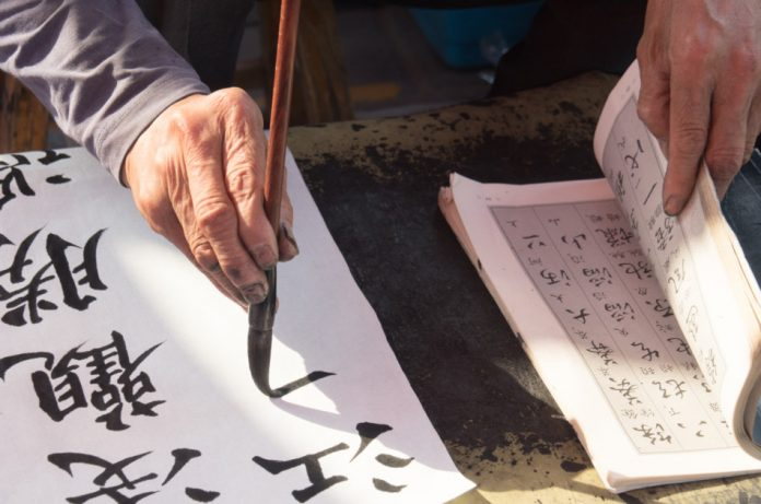 A calligrapher hand writing chinese calligraphy.