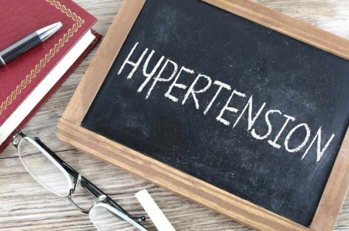 Small chalkboard with the word 'hypertension' written on it sits on a wooden surface next to a book with a red cover, a black ball point pen, a pair of reading glasses, and a piece of chalk.