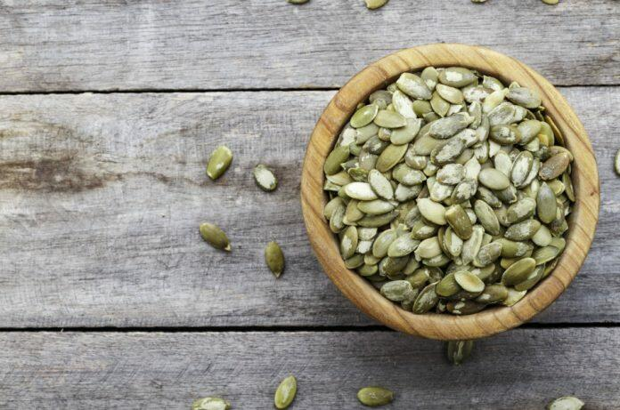 A bowl of peeled pumpkin seeds sits on a wooden surface.